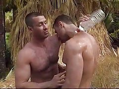Muscle gay dilfs caress each other in jungle