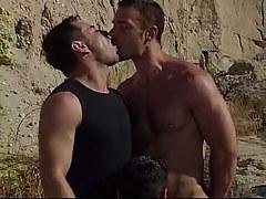 Cute gay boy serves two dilfs in desert